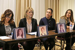 FILE - In this Monday, Dec. 2, 2019 file photo, sisters Patty Fortney-Julius, Lara Fortney McKeever, second from left, Teresa Forteny-Miller, second from right, and Carolyn Fortney sit behind pictures of themselves as children as they listen to an attorney speak to reporters during a news conference in Newark, N.J. Two of the sisters from Pennsylvania, Patty and Lara, are suing the Archdiocese of Newark and the Diocese of Harrisburg, Pa. They allege clergy in Newark knew a priest had sexually abused children before he moved to Harrisburg and abused them and their sisters for years. In their latest annual report on clergy sex abuse released on Thursday, June 25, 2020, U.S. Catholic bishops say there were 4,434 allegations against clergy in 2018-19, triple the previous year – with much of the increase stemming from a new wave of lawsuits and claims by survivors of decades-old molestation.  (AP Photo/Seth Wenig)