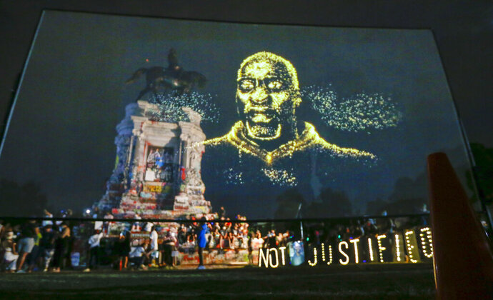 An image of George Floyd is projected on a screen in front of the statue of Confederate General Robert E. Lee on Monument Avenue Tuesday July 28, 2020, in Richmond, Va. Change.org and the George Floyd Foundation officially launched