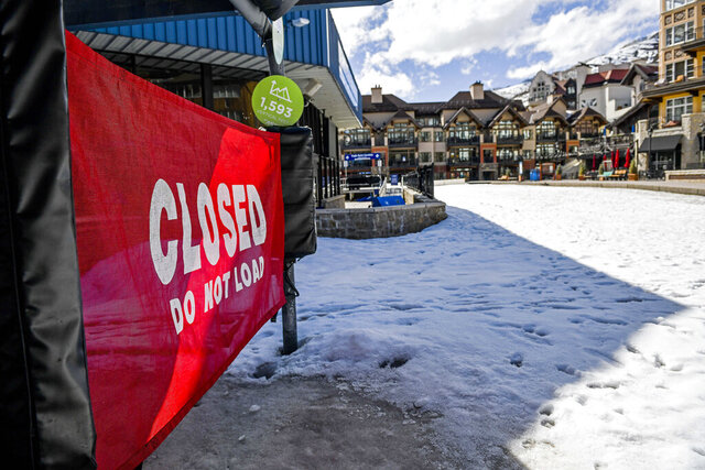 In this Tuesday, March 24, 2020, photo a sign hangs on a closed ski lift in Vail, Colo., after Vail Ski Resort closed for the season amid the COVID-19 pandemic. Ski resorts across the West that were shut down amid coronavirus fears are grappling with an economic