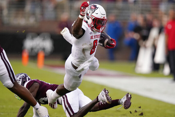 North Carolina State running back Ricky Person Jr. (8) is knocked into the air by a Mississippi State defender during the first half of an NCAA college football game in Starkville, Miss., Saturday, Sept. 11, 2021. (AP Photo/Rogelio V. Solis)