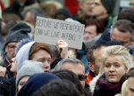 A man holds up a poster during a solidarity rally In Hanau, Germany Saturday, Feb. 22, 2020, three days after several people were killed in a shooting at the city. (AP Photo/Michael Probst)