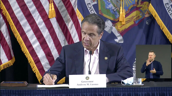 In this image made from video provided by the office of Gov. Andrew M. Cuomo, Gov. Cuomo signs a bill giving death benefits to the families of certain government workers who were killed by coronavirus, Saturday, May 30, 2020 in New York. (Office of Governor Andrew M. Cuomo via AP)