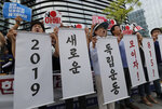 South Korean protesters hold signs during a rally denouncing the Japanese Prime Minister Shinzo Abe in front of the Japanese embassy in Seoul, South Korea, Thursday, Aug. 8, 2019. The letters read