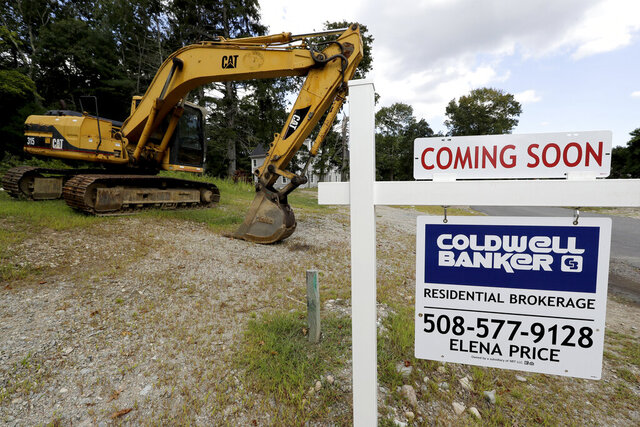FILE - In this Sept. 3, 2019, file photo a sign rests near a piece of earth-moving equipment, left, on a plot of land, in Westwood, Mass. On Tuesday, Dec. 17, the Commerce Department reports on U.S. home construction in November. (AP Photo/Steven Senne, File)