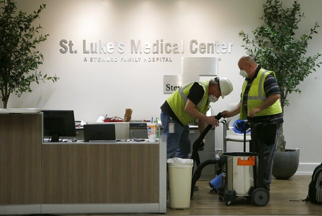 In this April 23, 2020, photo, contract workers join the Army Corps of Engineers as they get the currently dormant St. Luke's Hospital ready for reopening for the possible surge of coronavirus patients in Phoenix. As states gear up to reopen, a poll finds a potential obstacle to controlling coronavirus: nearly 1 in 10 adults say cost would keep them from seeking help if they thought they were infected. The Gallup-West Health Healthcare Costs Survey out Tuesday, April 28, finds that 9% of those age 18 and over would avoid seeking treatment because of concerns about the cost of care, even if they thought they were infected with the coronavirus.  (AP Photo/Ross D. Franklin)