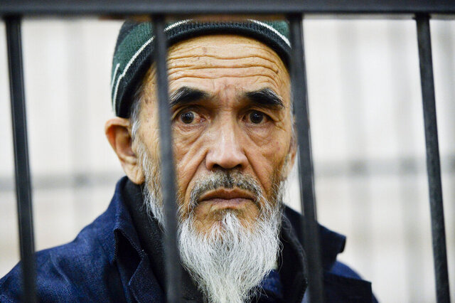 FILE - In this Tuesday, Oct. 11, 2016 file photo, Azimzhan Askarov, ethnic Uzbek human rights activist, who has been jailed for life for stirring up ethnic hatred in a case which has drawn international criticism, looks through a metal bars at a courtroom during hearings opened at the regional court in the capital Bishkek, Kyrgyzstan. Azimzhan Askarov, a human rights defender in Kyrgyzstan who was serving a life term on charges of involvement in inter-ethnic violence widely criticized as trumped-up, died Saturday July 25, 2020, in a prison clinic at the age of 69. (AP Photo/Vladimir Voronin, File)