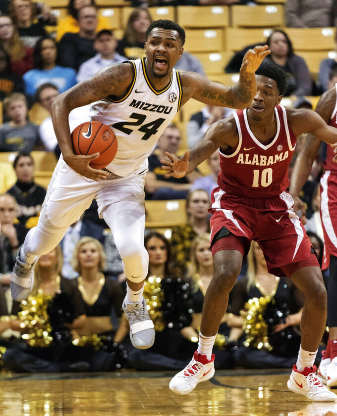Missouri's Kevin Puryear (24) tries to save the ball from going out of bounds in front of Alabama's Herbert Jones (10) during the first half of an NCAA college basketball game, Wednesday, Jan. 16, 2019, in Columbia, Mo. (AP Photo/L.G. Patterson)