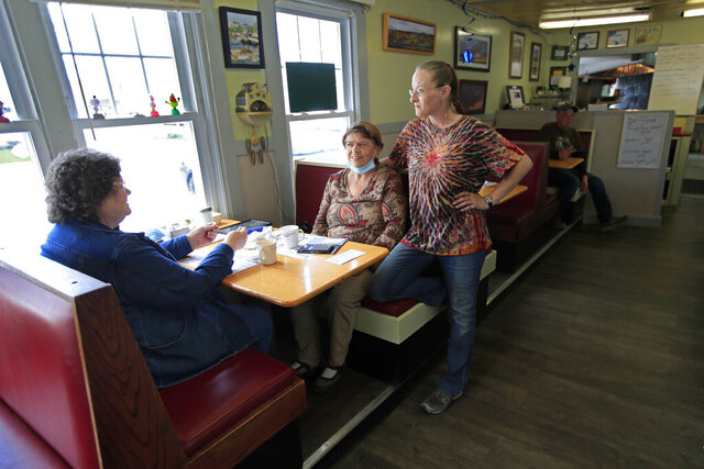 Tarah Diffen, far right, chats with customers at the Hot Spot Diner, Monday, May 18, 2020, in Wiscasset, Maine. Diffen's restaurant, which has been closed since March 22 because of the coronavirus, reopened on Monday. Governor Janet Mills is now allowing restaurants in 12 of the state's 16 counties to have dine-in customers.(AP Photo/Robert F. Bukaty)