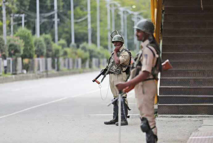 Indian paramilitary soldiers stand guard during a security lockdown in Srinagar, Indian controlled Kashmir, Monday, Aug. 12, 2019. Troops in India-administered Kashmir allowed some Muslims to walk to local mosques alone or in pairs to pray for the Eid al-Adha festival on Monday during an unprecedented security lockdown that still forced most people in the disputed region to stay indoors on the Islamic holy day. (AP Photo/Mukhtar Khan)