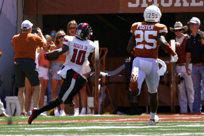 Texas Tech wide receiver Kaylon Geiger (10) runs for a touchdown after catching a long pass against Texas defensive back B.J. Foster (25) during the second half of an NCAA college football game on Saturday, Sept. 25, 2021, in Austin, Texas. (AP Photo/Chuck Burton)