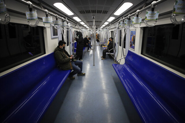 FILE - In this Feb. 17, 2020, file photo, commuters ride in a quiet subway train during the morning rush hour in Beijing. As many Chinese finally go back to work after their longest Lunar New Year holiday ever, the economic fallout from the outbreak of a new coronavirus that began in Wuhan may be just beginning. Companies are warning their bottom lines will take a hit, and governments are ramping up stimulus measures for economies that just weeks ago were hoping to see recoveries after months of uncertainty due to trade tensions and slowing global growth. (AP Photo/Andy Wong, File)