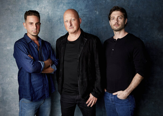 FILE - In this Jan. 24, 2019, file photo, Wade Robson, from left, director Dan Reed and James Safechuck pose for a portrait to promote the film