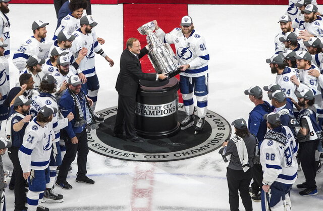 Tampa Bay Lightning's Steven Stamkos (91) is presented the Stanley Cup from NHL commissioner Gary Bettman as they celebrate after defeating the Dallas Stars in the NHL Stanley Cup hockey finals, in Edmonton, Alberta, on Monday, Sept. 28, 2020. (Jason Franson/The Canadian Press via AP)