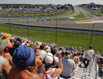 FILE - In this Aug. 5, 2018, file photo, spectators watch as drivers come around Turn 1 during a restart after a caution during a NASCAR Cup Series auto race in Watkins Glen, N.Y. NASCAR will move its August road course race from Watkins Glen in upstate New York because of state health restrictions, and the event will shift instead to the road course at Daytona International Speedway. NASCAR'S August schedule revisions announced Wednesday, July 8, 2020, cover six Cup races at three tracks.  (AP Photo/Julie Jacobson, File)
