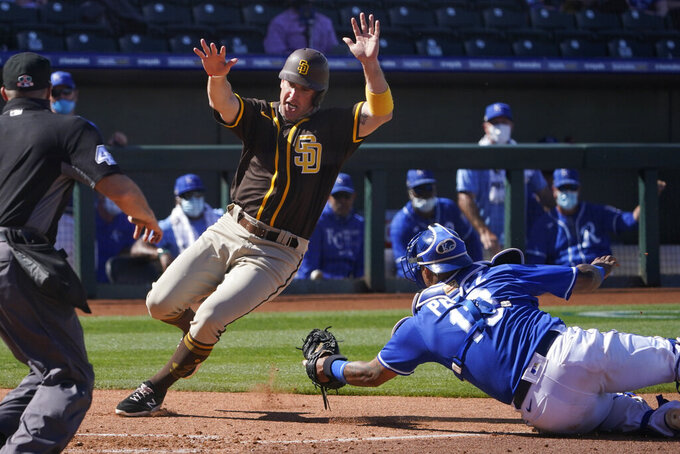 San Diego Padres' Patrick Kivlehan, left, avoids a tag by Kansas City Royals catcher Salvador Perez to score on a single by Brian O'Grady during the sixth inning of a spring training baseball game Monday, March 22, 2021, in Surprise, Ariz. (AP Photo/Sue Ogrocki)