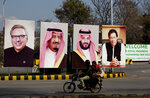 FILE - In this Feb. 15, 2019  file photo, Pakistani riders drive past portraits of Pakistani and Saudi leaders displayed on the occasion of a visit by Saudi Arabia's Crown Prince to Pakistan, in Islamabad, Pakistan. Amid the Kashmir crisis, Gulf Arab states balance relations with Muslim-majority Pakistan and trade partner India. Saudi Arabia's response to the Kashmir situation is complicated by its close ties with both India and Pakistan, which have fought two wars over the disputed Himalayan region, as well as its ideological rivalry with Turkey and Iran for supremacy in the Islamic world. (AP Photo/B.K. Bangash, File)
