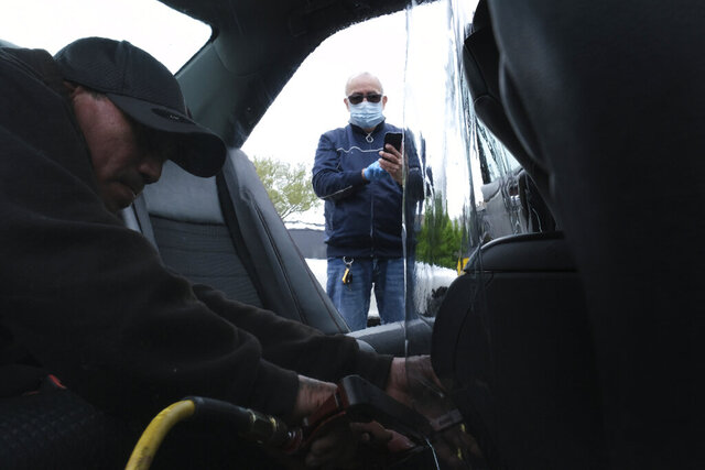FILE - In this Wednesday, May 6, 2020, file photo, Luis Hidalgo, wearing face mask, watches as Joel Rios installs a plastic barrier in his car to protect himself and his passengers from the new coronavirus in the Bronx borough of New York. Hidalgo, who drives sometimes for Uber, said he has not worked for two months for fear of the coronavirus but mounting bills have forced him back to work; he hopes the plastic barrier will keep him and his passengers safe. (AP Photo/Seth Wenig, File)