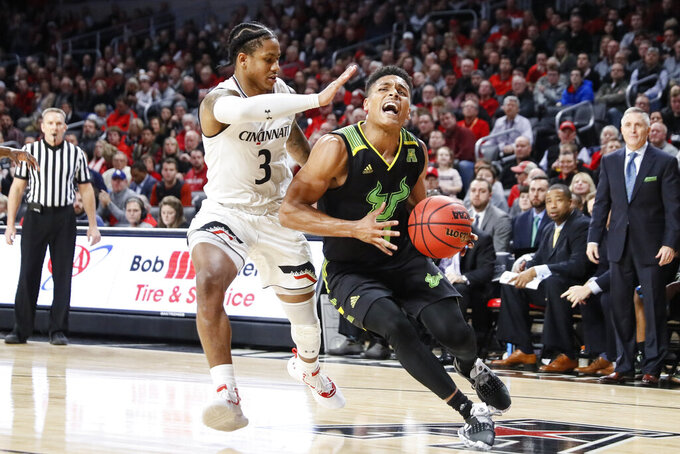 South Florida's Xavier Castaneda, right, drives against Cincinnati's Justin Jenifer (3) in the second half of an NCAA college basketball game, Tuesday, Jan. 15, 2019, in Cincinnati. (AP Photo/John Minchillo)