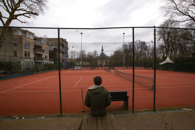 A man talks on his mobile phone outside a closed tennis club in Amsterdam, Netherlands, Wednesday, March 18, 2020. The Dutch government ordered all Dutch schools, cafes, restaurants, coffeeshops, sex clubs and sport and fitness clubs to be closed as the government sought to prevent the further spread of coronavirus in the Netherlands. For most people, the new coronavirus causes only mild or moderate symptoms, such as fever and cough. For some, especially older adults and people with existing health problems, it can cause more severe illness, including pneumonia. (AP Photo/Peter Dejong)