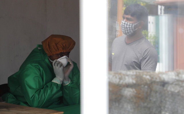 A Sri Lankan municipal health worker takes a breather while collecting swab samples to test for COVID-19, as a man waiting for his turn to test is seen reflected on a window in Colombo, Sri Lanka, Friday, July 10, 2020. (AP Photo/Eranga Jayawardena)