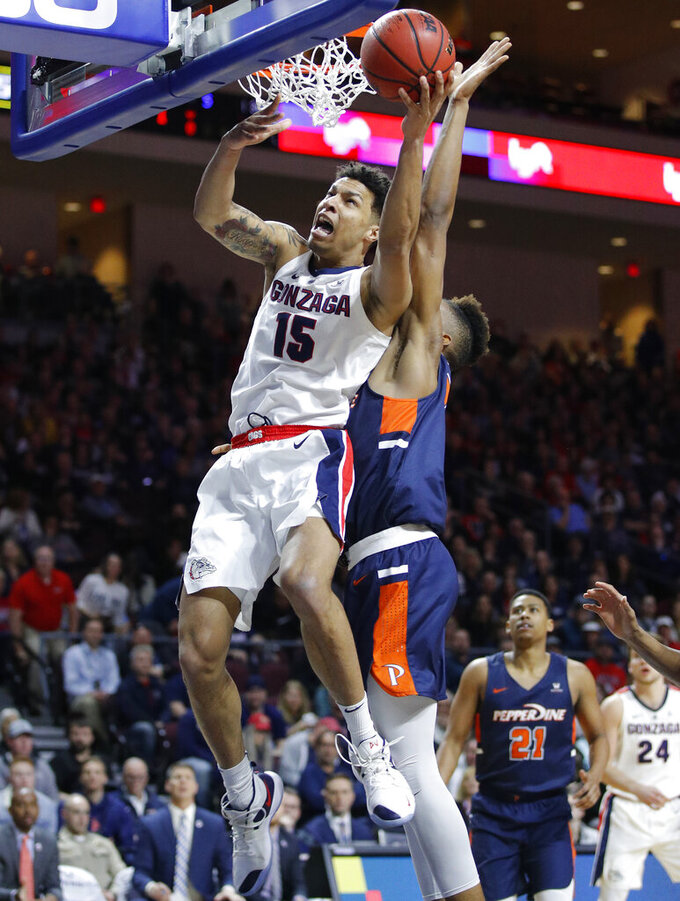 Gonzaga's Brandon Clarke (15) shoots around Pepperdine's Victor Ohia Obioha during the first half of an NCAA semifinal college basketball game at the West Coast Conference tournament, Monday, March 11, 2019, in Las Vegas. (AP Photo/John Locher)