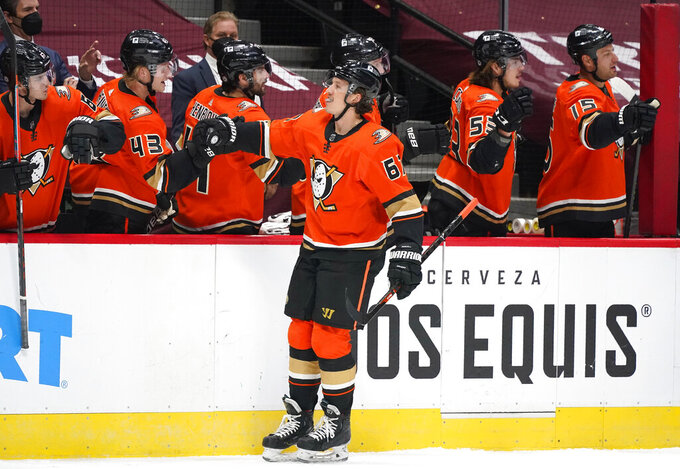 FILE - In this Saturday, March 6, 2021 file photo, Anaheim Ducks center Rickard Rakell, front, is congratulated as he passes the team box after scoring a goal against the Colorado Avalanche during the first period of an NHL hockey game in Denver. Rakell is one of the few players signed beyond this season who could be moved at the NHL trade deadline. (AP Photo/David Zalubowski, File)
