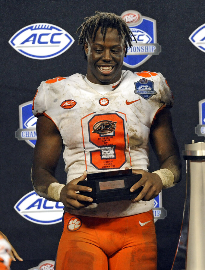 Clemson's Travis Etienne (9) holds to trophy for being named the game's most valuable player after Clemson defeated Pittsburgh to win the Atlantic Coast Conference championship NCAA college football game in Charlotte, N.C., Saturday, Dec. 1, 2018. (AP Photo/Mike McCarn)