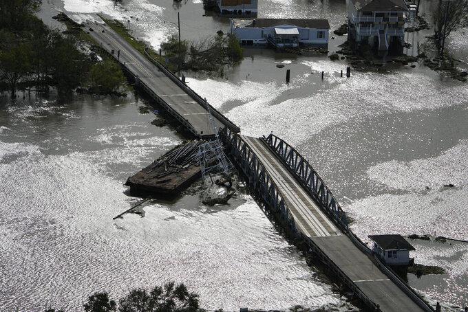 A barge damages a bridge that divides Lafitte, La., and Jean Lafitte, in the aftermath of Hurricane Ida, Monday, Aug. 30, 2021, in Lafitte, in La. (AP Photo/David J. Phillip)