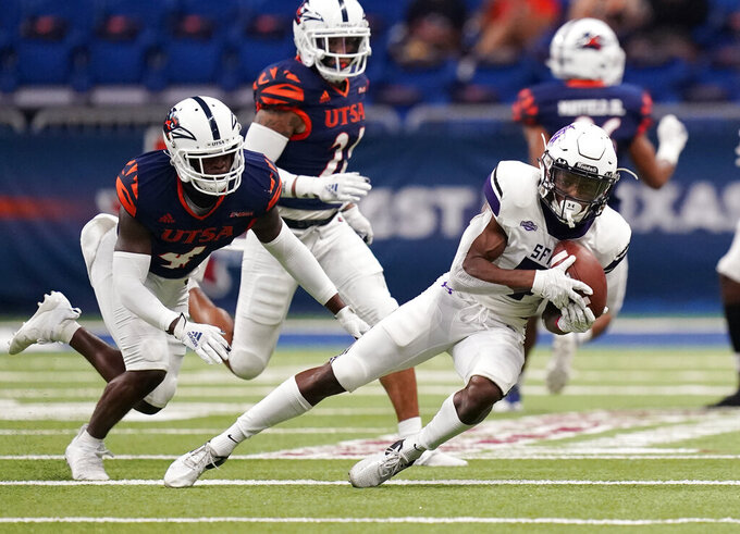 Stephen F. Austin wide receiver Remi Simmons (9) makes a catch in front of UTSA safety Antonio Parks (4) during the first half of an NCAA college football game, Saturday, Sept. 19, 2020, in San Antonio. (AP Photo/Eric Gay)