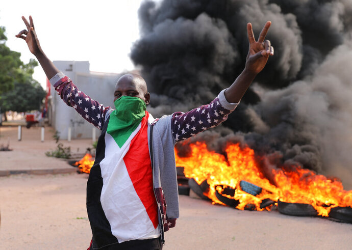 A demonstrator gives the victory sign at a protest, in Khartoum, Sudan, Wednesday, Oct. 21, 2020. Protesters have taken to the streets in the capital and across the country over dire living conditions and a deadly crackdown on demonstrators in the east earlier this month. Sudan is currently ruled by a joint civilian-military government, following the popular uprising that toppled longtime autocrat Omar al-Bashir last year. (AP Photo/Marwan Ali)