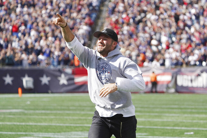 Former New England Patriots wide receiver Julian Edelman acknowledges fans as he runs onto the field while being honored at halftime of an NFL football game against the New Orleans Saints, Sunday, Sept. 26, 2021, in Foxborough, Mass. (AP Photo/Mary Schwalm)