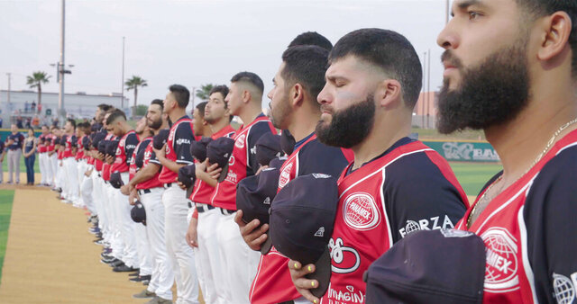 Members of the Tecolotes de los Dos Laredo, a binational professional baseball team with home stadiums in Nuevo Laredo, Mexico, and Laredo, Texas, stand for the U.S. National Anthem before a game in 2019 in Laredo, Texas in a scene from