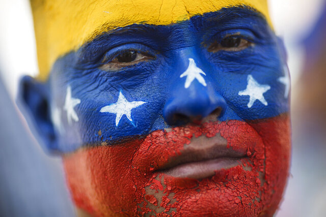 In this Saturday, Nov. 16, 2019 photo, May Vera eyes the camera during a demonstration led by opposition politician Juan Guaido, who's urging masses into the streets to force President Nicolás Maduro from power, in Maracaibo, Venezuela. Vera's face was painted by his niece with the colors of Venezuela's national colors. Guaido called nationwide demonstrations to re-ignite a campaign against Maduro launched in January that has lost steam in recent months. (AP Photo/Rodrigo Abd)