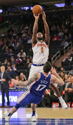 Philadelphia 76ers' JJ Redick, bottom, falls as New York Knicks' Emmanuel Mudiay shoots during the second half of the NBA basketball game, Sunday, Jan. 13, 2019, in New York. (AP Photo/Seth Wenig)