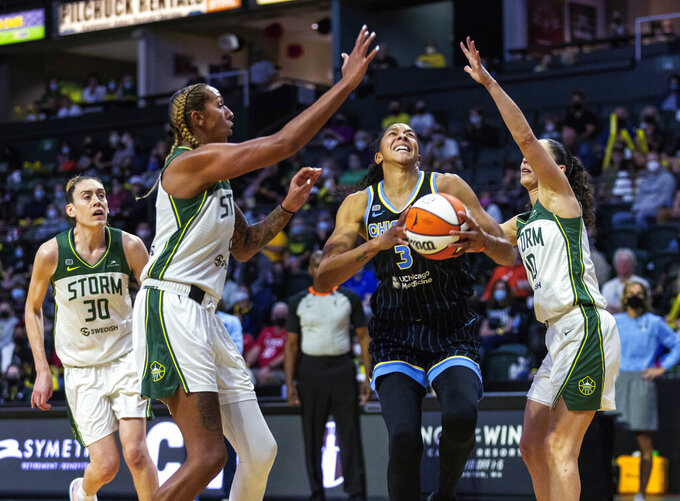 Chicago Sky's Candace Parker drives between Seattle Storm's Mercedes Russell, left, and Sue Bird during the first quarter of a WNBA basketball game Friday, Aug. 27, 2021, in Everett, Wash. (Dean Rutz/The Seattle Times via AP)
