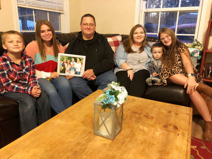 Keith Michael, third from left, sits on a sofa with his children, from left, Hunter, Jessica, Sara, Houston and Holly, at their home on Friday, Nov. 13, 2020, in Jonesboro, Ark. Among the victims of the coronavirus is Michael's wife, fourth-grade Arkansas teacher Susanne Michael, who died less than three months after celebrating the adoption of three of the children. (AP Photo/Adrian Sainz)