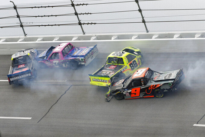 Ben Rhodes (99), Sheldon Creed (2), Matt Crafton (88) and Codie Rohrbaugh (9) wreck on one of the last laps during a NASCAR Truck Series auto race Saturday, Oct. 2, 2021, in Talladega, Ala. (AP Photo/Russell Norris)
