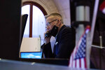 Trader Neil Catania works on the floor of the New York Stock Exchange, Friday, July 23, 2021. Stocks rose in early trading on Wall Street Friday and put the major indexes on track for a strong finish in a week that opened with a stumble. (AP Photo/Richard Drew)
