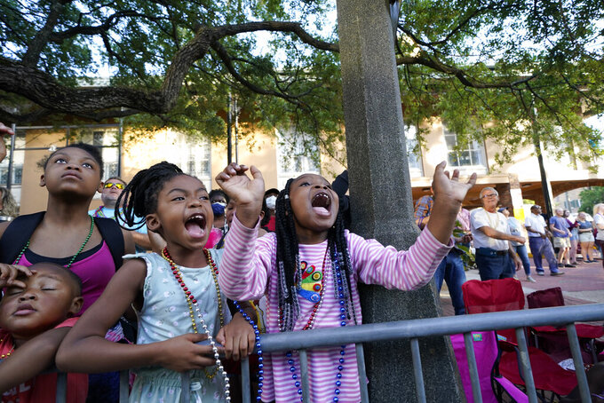 """Children scream for throws during a parade dubbed """"Tardy Gras,"""" to compensate for a cancelled Mardi Gras due to the COVID-19 pandemic, in Mobile, Ala., Friday, May 21, 2021. (AP Photo/Gerald Herbert)"""