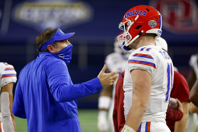 Florida coach Dan Mullen talks with quarterback Kyle Trask after Trask threw a pass into the end zone that was intercepted by Oklahoma's Woodi Washington during the first half of the Cotton Bowl NCAA college football game in Arlington, Texas, Wednesday, Dec. 30, 2020. (AP Photo/Ron Jenkins)