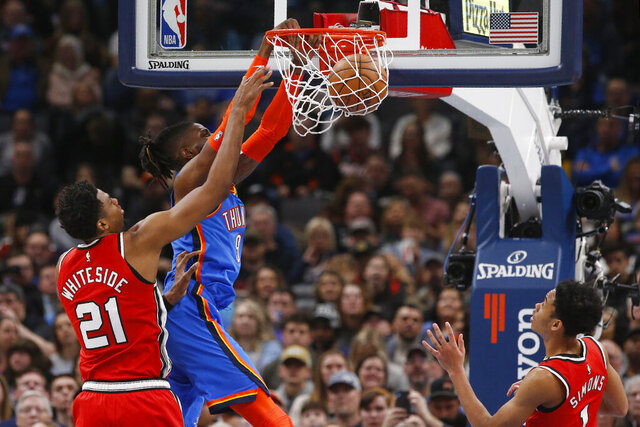 Oklahoma City Thunder center Nerlens Noel (9) dunks between Portland Trail Blazers center Hassan Whiteside (21) and guard Anfernee Simons (1) in the first half of an NBA basketball game Saturday, Jan. 18, 2020, in Oklahoma City. (AP Photo/Sue Ogrocki)