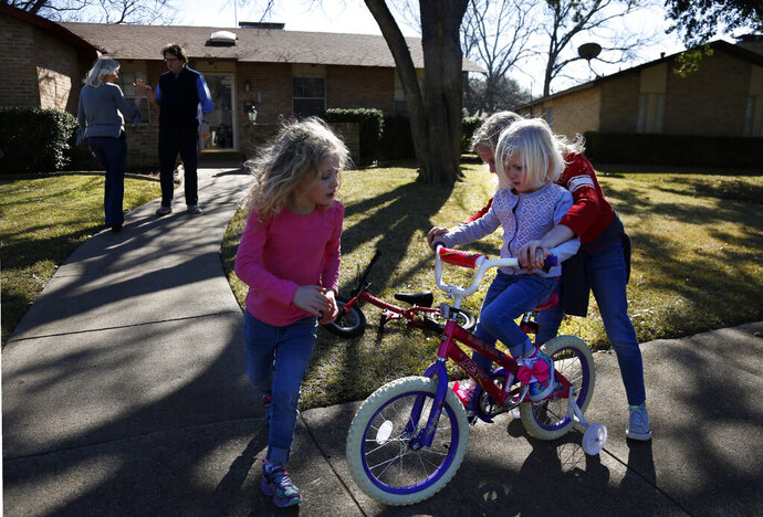 In this Feb. 8, 2020, photo, Alli Whitfield, left, high-fives husband and Catholic Priest Joshua, as their three daughters Zoe-Catherine, 5, Bernadette, 4, and Maggie, 9, ride bikes outside of their home in north Dallas. (AP Photo/Jessie Wardarski)