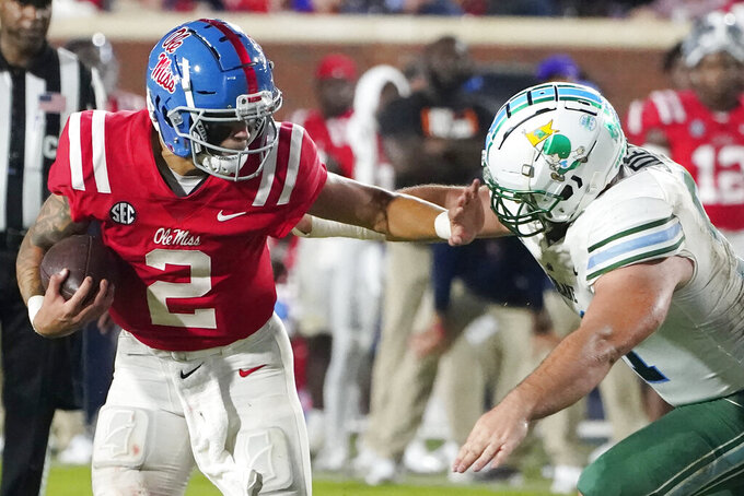 Mississippi quarterback Matt Corral (2) stiff-arms a Tulane defender during the first half of an NCAA college football game, Saturday, Sept. 18, 2021, in Oxford, Miss. (AP Photo/Rogelio V. Solis)
