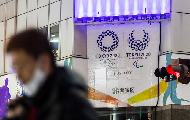 A man walks past Tokyo's promotional banners for its rescheduled Olympic games to be held in the summer 2021, in Tokyo on Thursday, Jan. 28, 2021. (AP Photo/Hiro Komae)