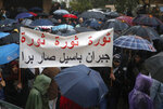 FILE - In this Sunday, Jan. 5, 2020 file photo, anti-government protesters hide under their umbrellas from the heavy rain, as they hold an Arabic banner that reads: