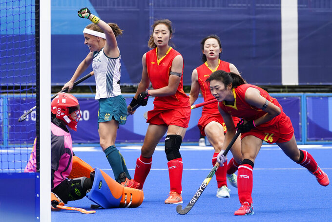 Australia's Emily Chalker, second from left, reacts after scoring on China goalkeeper Dongxiao Li, left, during a women's field hockey match at the 2020 Summer Olympics, Monday, July 26, 2021, in Tokyo, Japan. (AP Photo/John Minchillo)