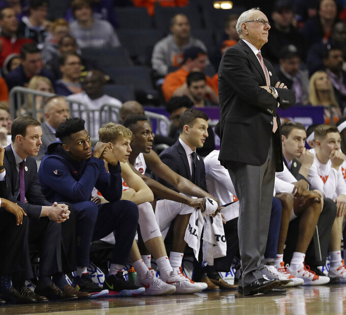 Syracuse's Tyus Battle, second from left, looks around head coach Jim Boeheim to watch the action against Pittsburgh during the first half of an NCAA college basketball game in the Atlantic Coast Conference tournament in Charlotte, N.C., Wednesday, March 13, 2019. Battle did not play in the game due to an injury. (AP Photo/Chuck Burton)
