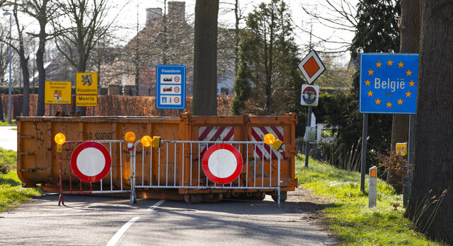 A container and barriers block a backroad used by locals on the Netherlands border with Belgium between Chaam, southern Netherlands, and Meerle, northern Belgium, Monday, March 23, 2020. Both countries have come to a near standstill as their governments sought to prevent the further spread of coronavirus. For most people, the new coronavirus causes only mild or moderate symptoms, such as fever and cough. For some, especially older adults and people with existing health problems, it can cause more severe illness, including pneumonia. (AP Photo/Peter Dejong)