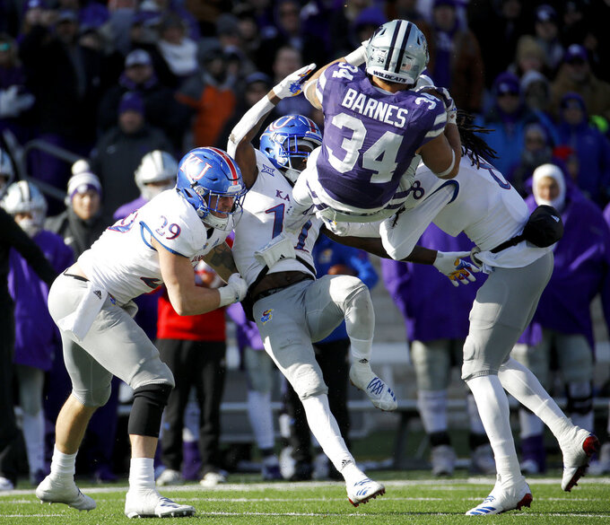 Kansas State running back Alex Barnes (34) is tackled by Kansas linebacker Joe Dineen Jr. (29), safety Mike Lee (11) and cornerback Shakial Taylor (8) during the second half of an NCAA college football game Saturday, Nov. 10, 2018, in Manhattan, Kan. Kansas State won 21-17. AP Photo/Charlie Riedel)