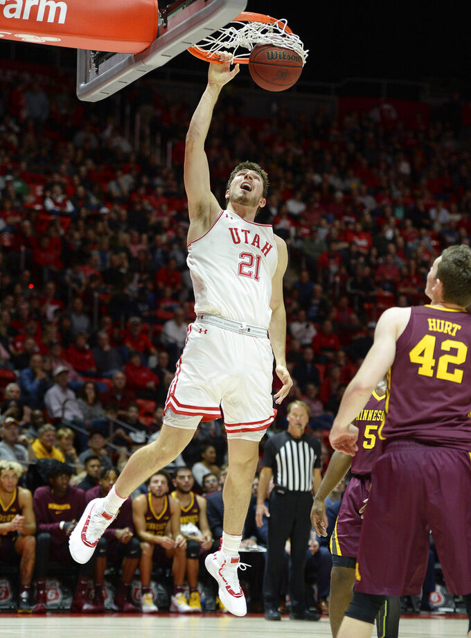 Utah forward Riley Battin (21) dunks as Minnesota's Michael Hurt watches during an NCAA college basketball game Friday, Nov. 15, 2019, in Salt Lake City. (Francisco Kjolseth/The Salt Lake Tribune via AP)